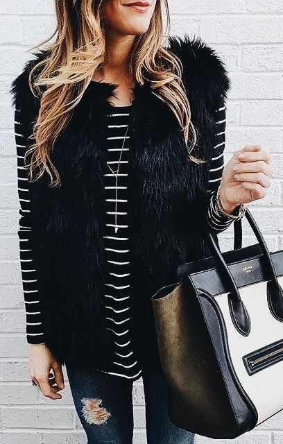 Black faux fur vest over black and white striped top with blue jeans. Love the c…