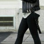 Trendy black leather moto jacket over cozy gray sweater and black pants with chi...
